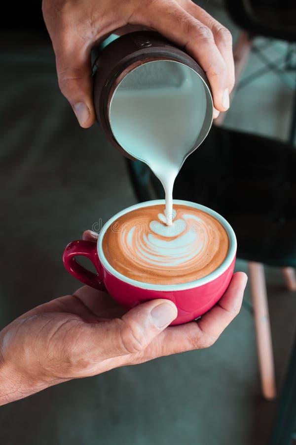 Il processo di versamento del latte dal lanciatore fa l'arte del latte del caffè da Baris fotografia stock