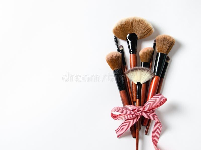 Il professionista compone l'arco rosso delle spazzole legato su fondo rosa pastello Copi lo spazio Magazin, media sociali fotografie stock libere da diritti