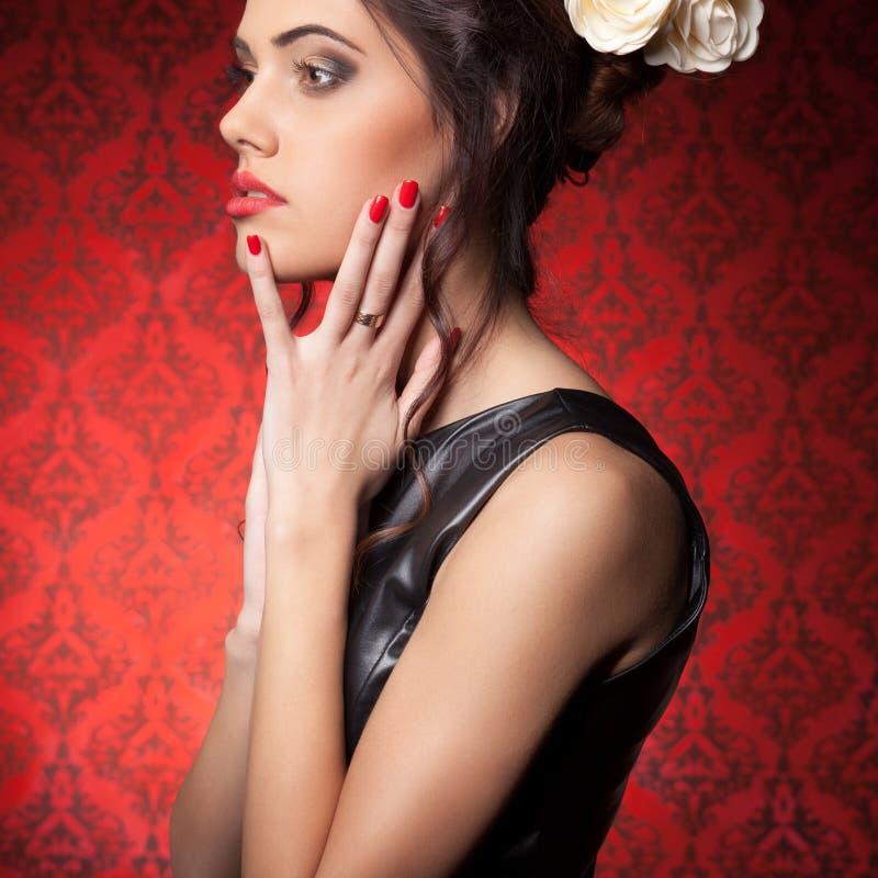 Il professionista sensuale della donna compone nella stanza d'annata rossa immagini stock
