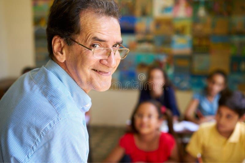 Il professor amichevole Smiling At Camera di In Class Happy dell'insegnante fotografia stock libera da diritti