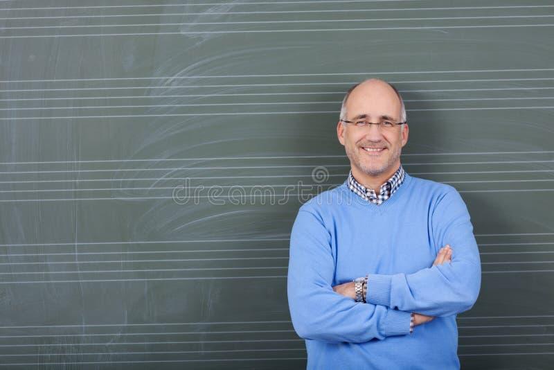 Il professor With Hands Folded che sta contro la lavagna immagini stock