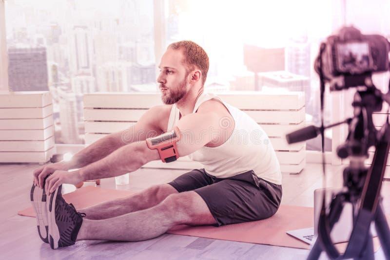 Il profilo dell'atleta concentrato che fa l'allungamento si esercita sul pavimento fotografia stock