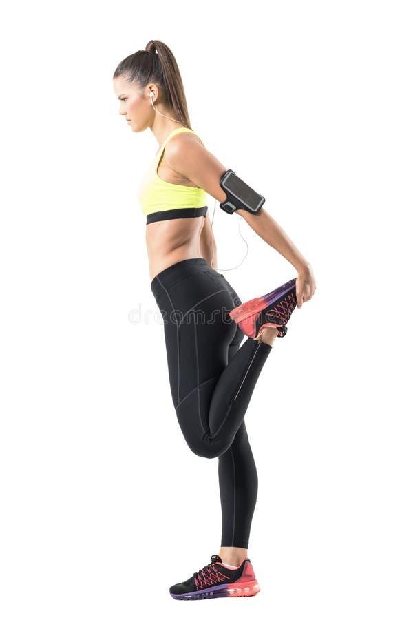 Il profilo della donna atletica che fa la gamba che allunga il quadricipite si esercita sulla singola gamba immagini stock libere da diritti