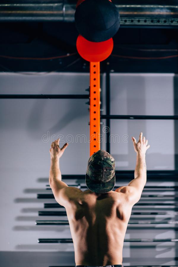 Il profilo di giovane atleta maschio si è accovacciato facendo gli esercizi delle palle della parete alla palestra immagine stock libera da diritti