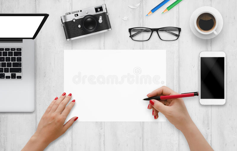 Il progettista scrive su una carta in bianco Visualizzazione superiore dello scrittorio del lavoro con il computer, telefono, mac fotografie stock libere da diritti