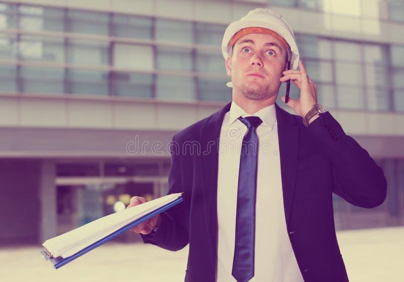 Il progettista in vestito e cappello con la cartella sta prendendo la cartella ed il disco fotografia stock libera da diritti