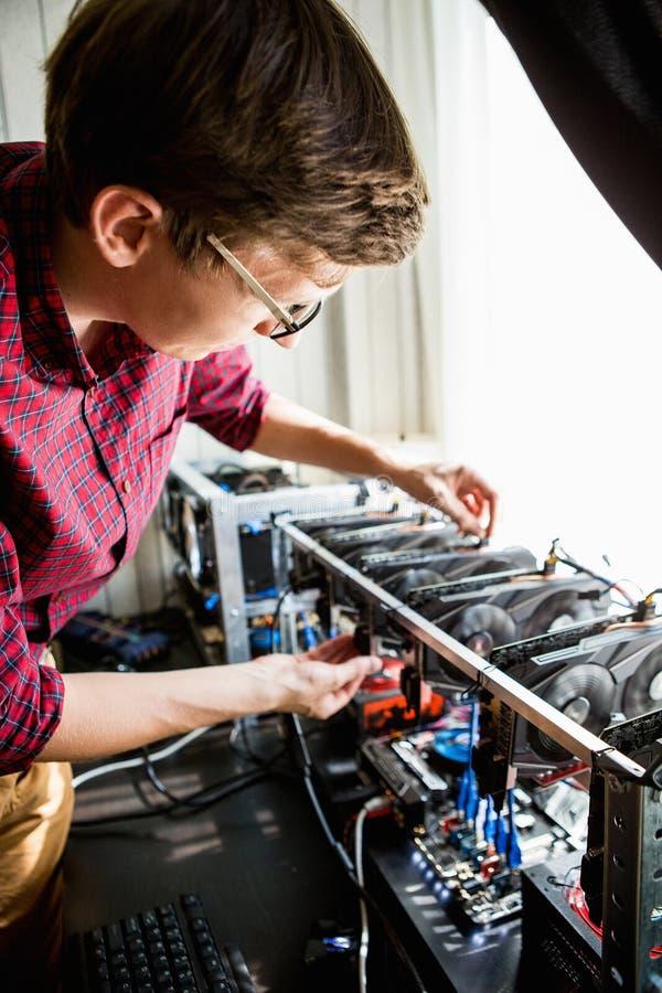 Il programmatore configura l'hardware per estrazione mineraria del bitcoin immagine stock