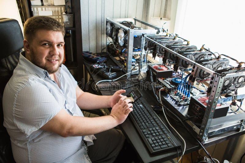 Il programmatore configura l'hardware per estrazione mineraria del bitcoin fotografie stock libere da diritti