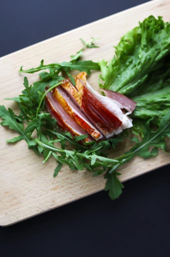Il prosciutto affettato con lattuga verde fresca va su un tagliere fotografia stock
