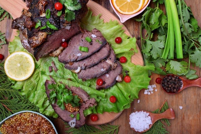 Il prosciutto cotto della carne degli alci incide le fette completate con pianta ed i mirtilli rossi fotografie stock libere da diritti