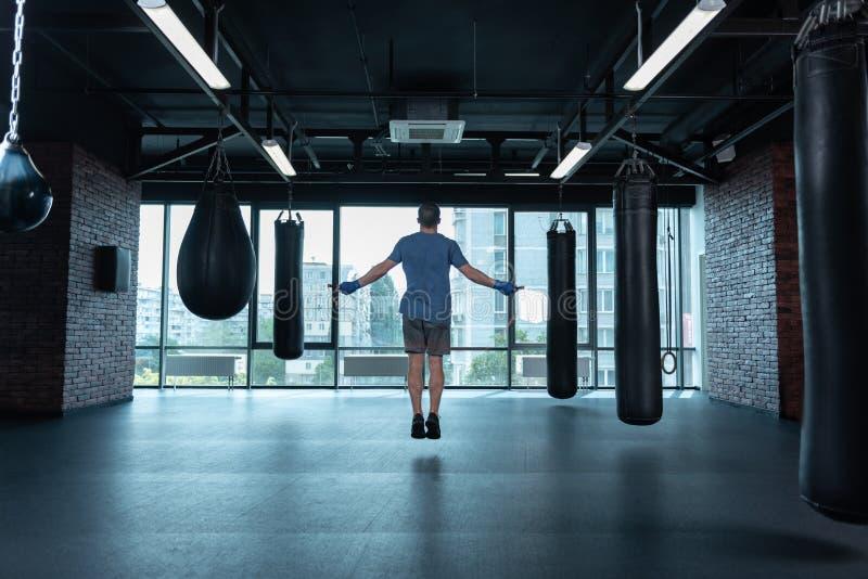 Il pugile atletico che indossa il polso blu avvolge la corda di salto immagine stock