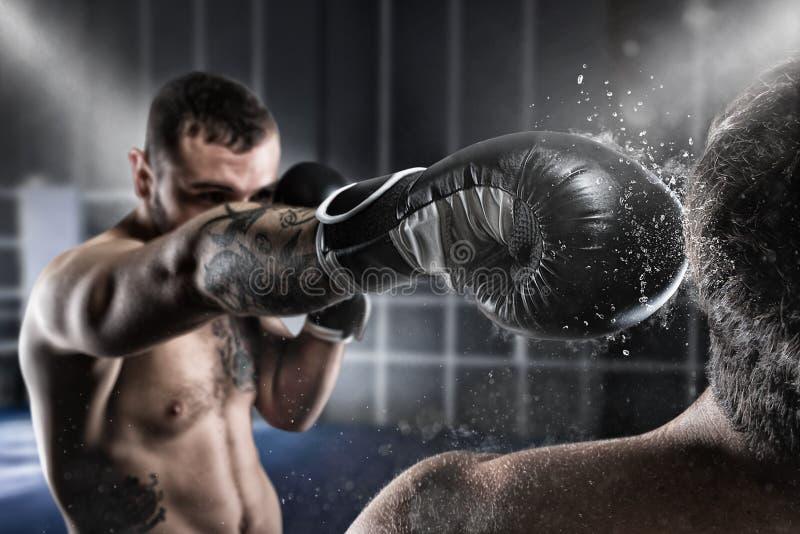 Il pugile in una concorrenza del boxe batte il suo oppositore fotografie stock
