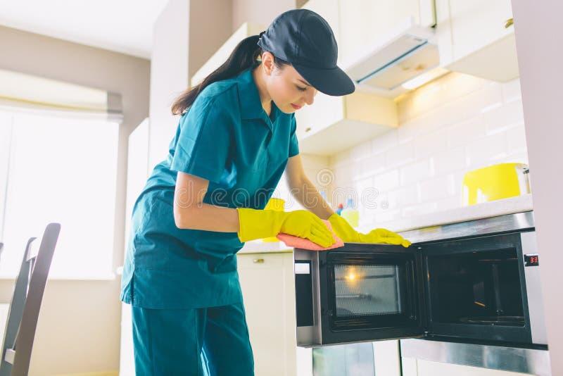Il pulitore sta in cucina e pulisce la superficie di microvawe Owen Lo fa con i guanti e lo straccio La ragazza è calma e fotografia stock