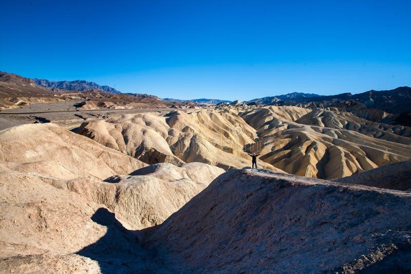 Il punto Death Valley, la California di Zabriskie, un singolo carattere sta gettando le sue mani su nell'aria fotografia stock