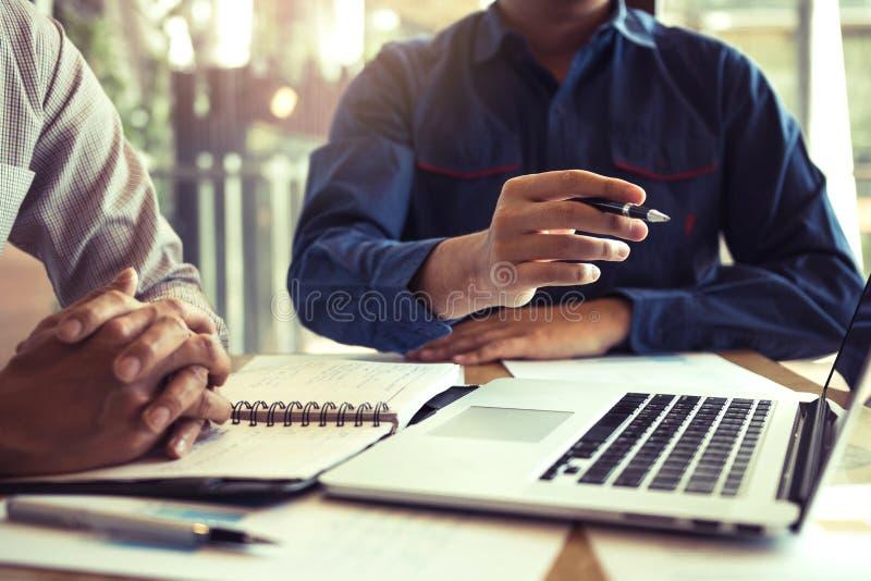 Il punto dell'uomo d'affari al grafico dei rendiconti finanziari della società riferisce nello schermo di computer che dà una pre fotografia stock