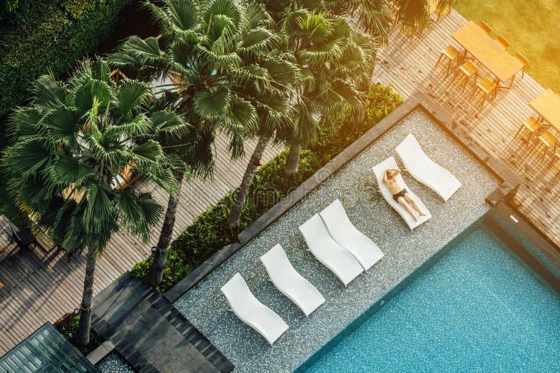 Il punto di vista di Arial del turista indica sulle sedie all'aperto vicino alla piscina con le palme nell'area dell'hotel immagine stock libera da diritti