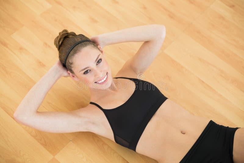 Il punto di vista dell'angolo alto della donna che snella sportiva fare si siede aumenta nella palestra immagine stock