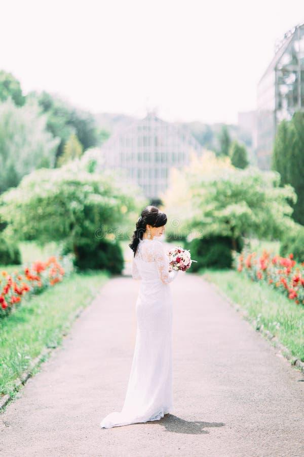 Il punto di vista integrale posteriore della sposa nel vestito bianco lungo che tiene il mazzo di nozze nel parco immagini stock