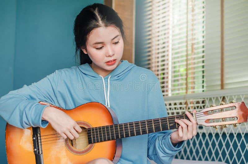 Il punto di vista parziale della ragazza asiatica che gioca sulla chitarra acustica a partire dalla mattina sveglia in camera da  immagini stock