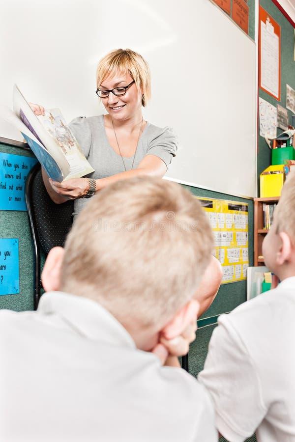 Il punto di vista posteriore dei bambini ascolta la storia di un insegnante immagine stock libera da diritti