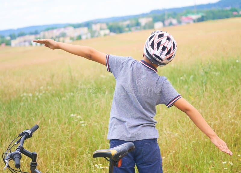 Il punto di vista posteriore del ragazzo dell'adolescente in casco protettivo ha sparso le sue armi fuori come una condizione del immagini stock