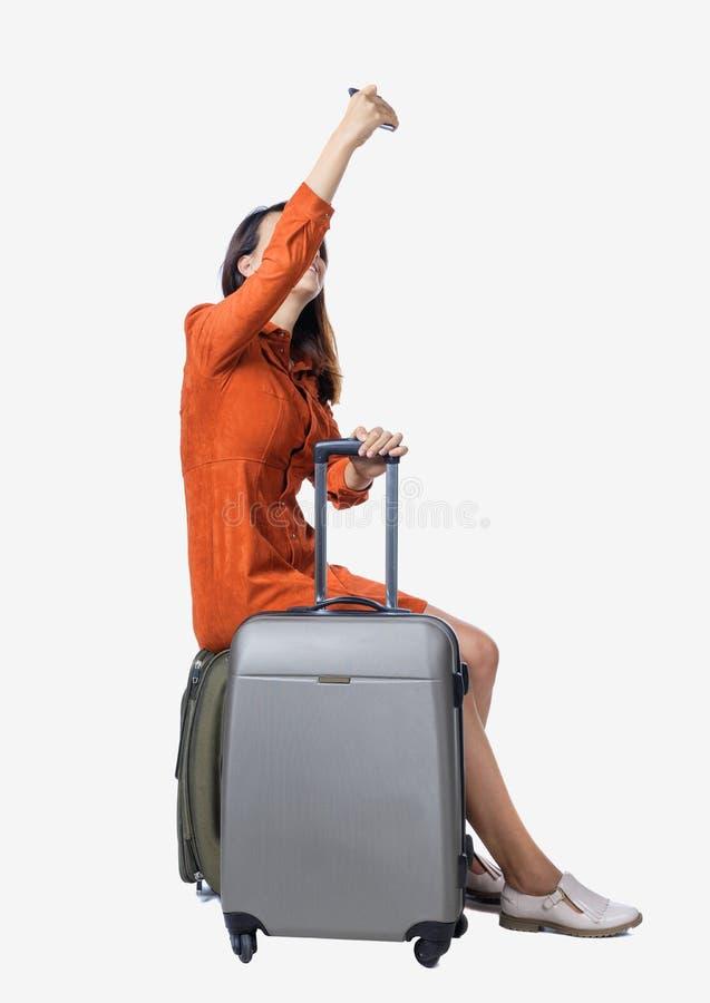 il punto di vista posteriore del viaggiatore della donna che si siede sulle valigie e fa il telefono del selfie fotografie stock libere da diritti