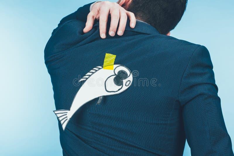 il punto di vista posteriore dell'uomo d'affari in vestito con carta ha fatto il pesce sopra appoggiare, pesci d'aprile immagini stock