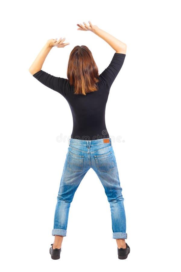 Il punto di vista posteriore della donna protegge le mani da che cosa sta cadendo dall'Abo fotografia stock libera da diritti