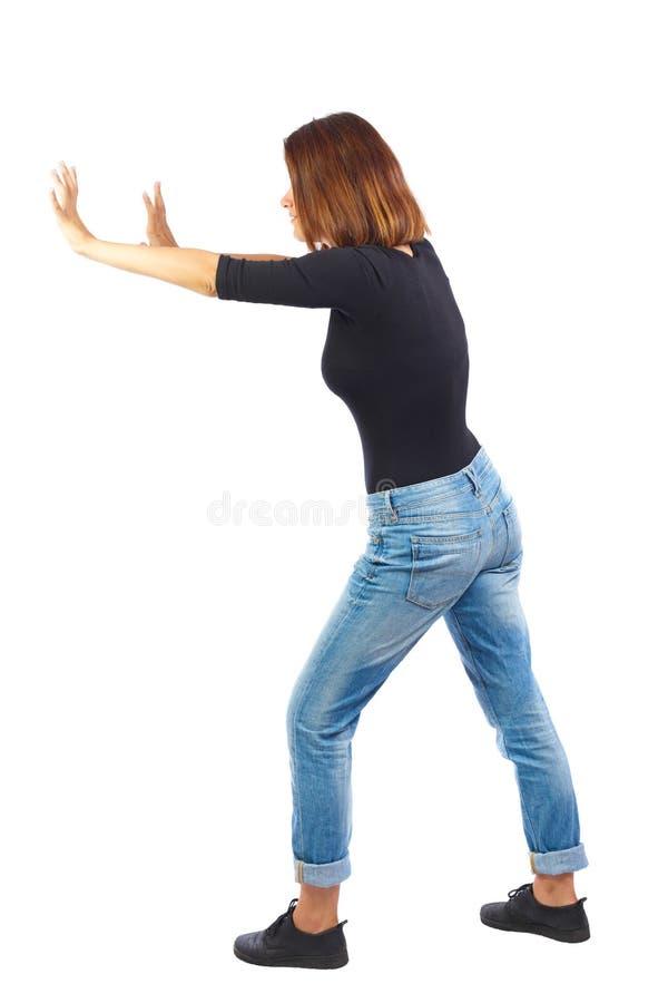 Il punto di vista posteriore della donna spinge la parete fotografia stock