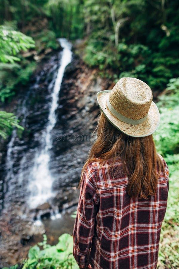 Il punto di vista posteriore della ragazza da lontano ammira la cascata fotografie stock libere da diritti
