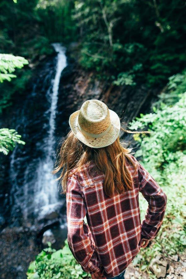 Il punto di vista posteriore della ragazza da lontano ammira la cascata fotografia stock