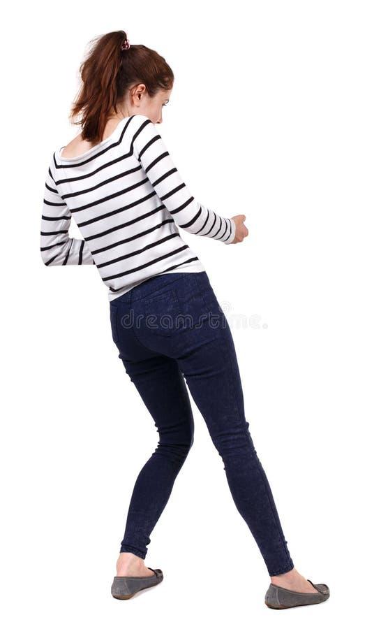 Il punto di vista posteriore della ragazza diritta che tira una corda dalla cima o aderisce alla s fotografia stock