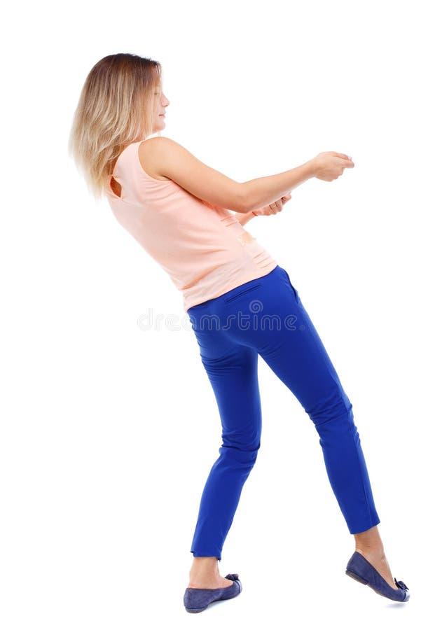Il punto di vista posteriore della ragazza diritta che tira una corda dalla cima o aderisce alla s immagini stock libere da diritti