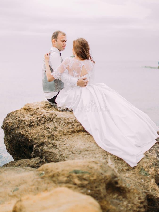 Il punto di vista posteriore delle persone appena sposate che si siedono sulla scogliera e che si esaminano ai precedenti del mar immagini stock