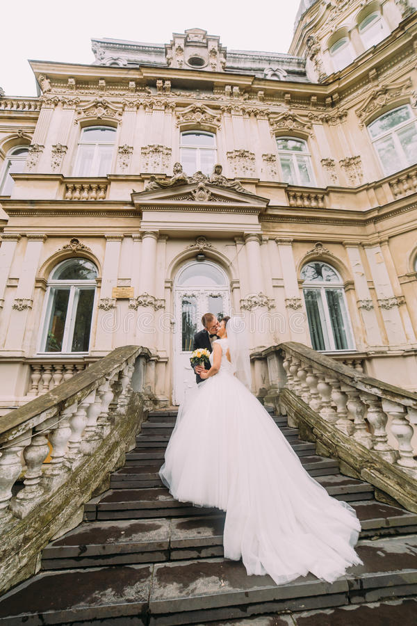 Il punto di vista posteriore delle persone appena sposate felici che stanno sulle scale di vecchia costruzione Lo sposo sta bacia fotografie stock libere da diritti