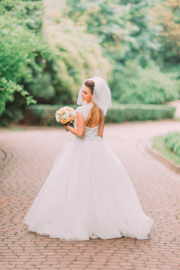 Il punto di vista posteriore integrale della sposa con la spalla nuda che tiene il mazzo di nozze ai precedenti del parco immagini stock