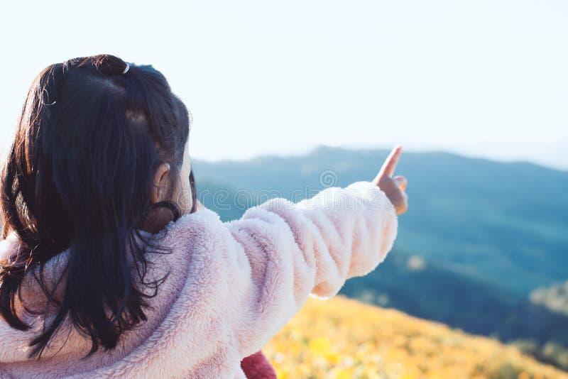 Il punto di vista posteriore di piccola ragazza asiatica del bambino ha messo sopra il cappotto alza il suo braccio fotografia stock libera da diritti