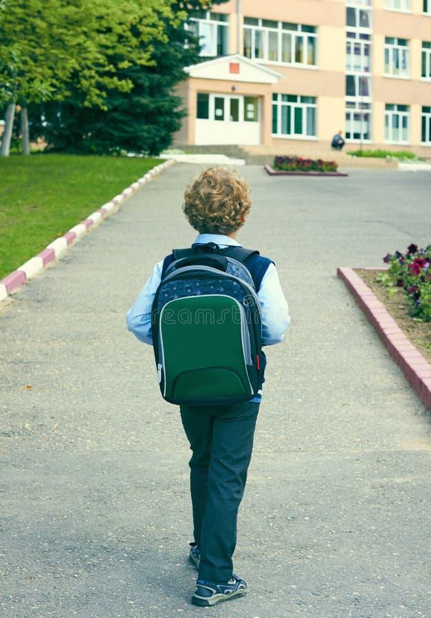 Il punto di vista posteriore di piccolo scolaro con uno zaino va a scuola esterno Istruzione, di nuovo al concetto della scuola immagini stock libere da diritti