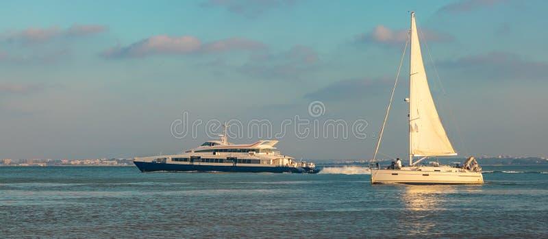 Il punto di vista scenico dei turisti spedisce e nave passeggeri nel fiume Lisbona, Portogallo di tejo in un bello tramonto Data  fotografie stock