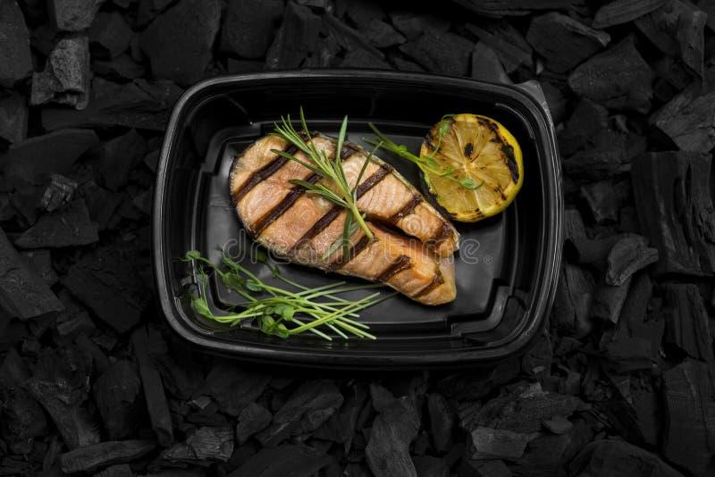 Il punto di vista superiore del pesce cucinato griglia dentro porta via la scatola su carbone fotografia stock