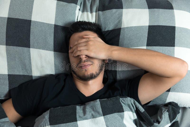 Il punto di vista superiore dell'uomo bello sbadiglia e sfrega i suoi occhi mentre dorme immagine stock