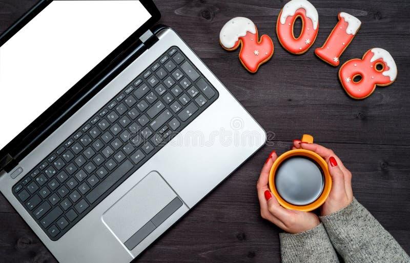 Il punto di vista superiore della donna passa la tenuta della tazza di caffè caldo, del computer portatile aperto con lo schermo  immagini stock libere da diritti