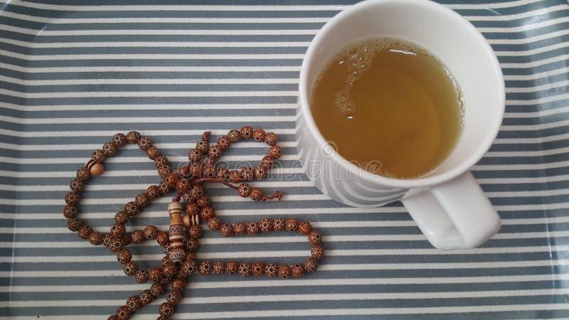 Il punto di vista superiore di tè verde in una tazza con le perle di preghiera o il rosario ha disposto in un vassoio immagine stock
