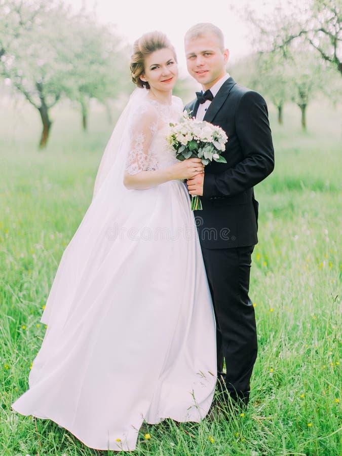 Il punto di vista verticale delle persone appena sposate felici ai precedenti del campo fotografia stock libera da diritti