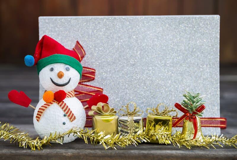 Il pupazzo di neve con il contenitore di regalo ed il Natale decorano l'insieme sopra la carta d'argento vaga di scintillio fotografie stock