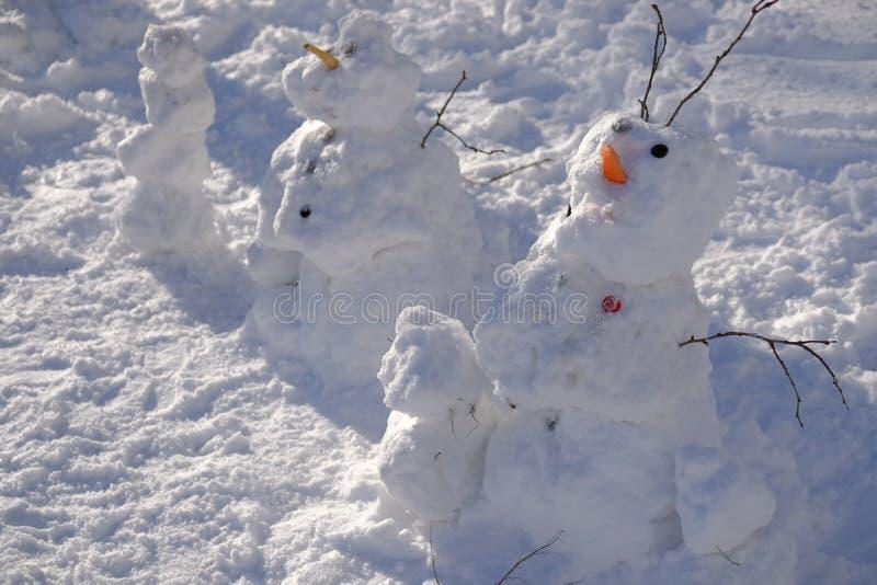Il pupazzo di neve spaventoso brutto fatto dai bambini su una via della città dell'inverno il giorno del Natale vacations immagini stock