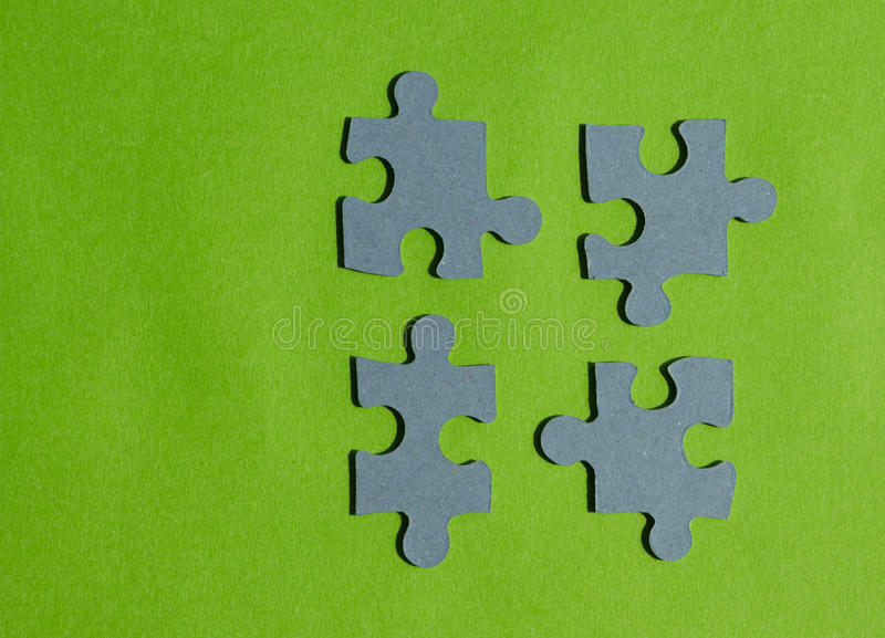 Il puzzle collega su fondo verde intenso, vista orizzontale fotografia stock