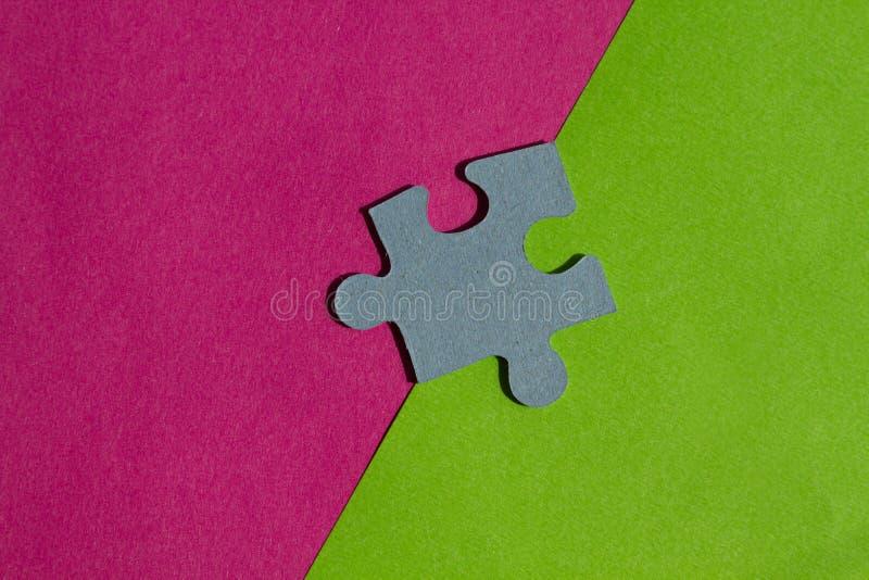 Il puzzle collega sul confine fra fondo rosa e verde fotografie stock