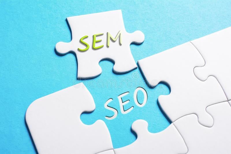 Il puzzle di SEO And SEM In Missing Piece Jigsaw di parole immagine stock
