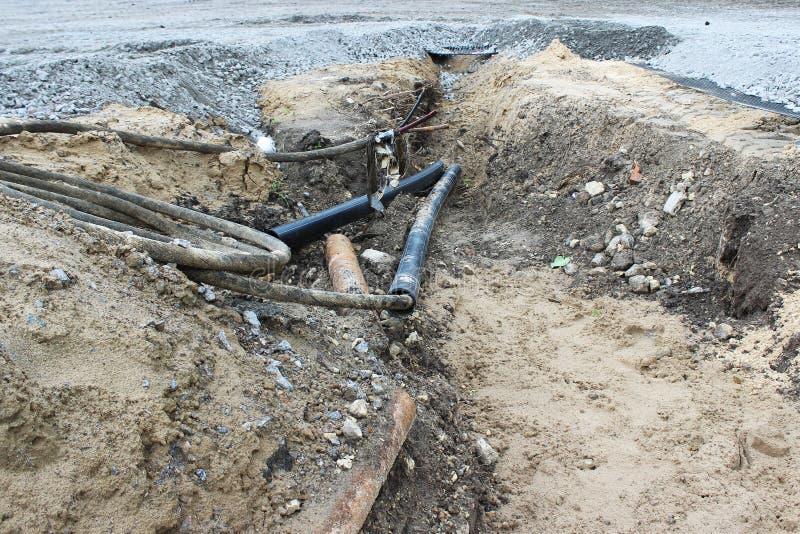 Il PVC protettivo ha ondulato il tubo con i cavi elettrici dentro, risieduto nella terra quando sviluppa un parcheggio per il tur fotografie stock